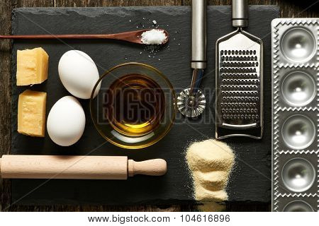 Kitchen utensils and ingredients for homemade pasta ravioli on slate