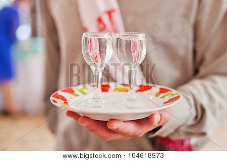 Two stemware  of vodka on a plate