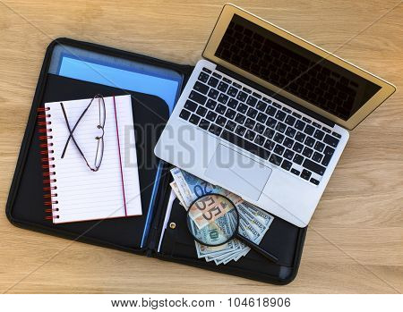 Folder for documents with dollar and Euro bills, Notepad, glasses and laptop on a wooden texture surface top view.