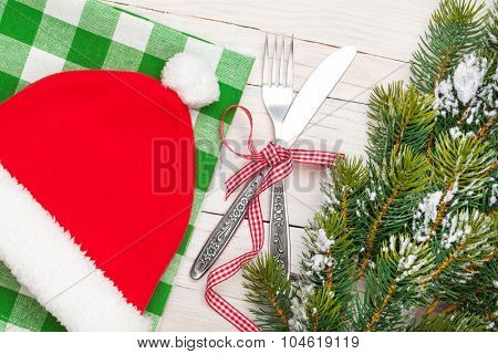 Santa hat, silverware and christmas tree. View from above over white wooden table background