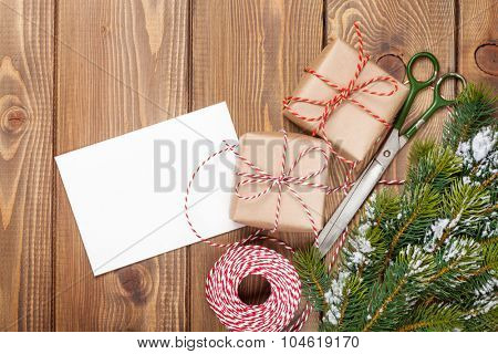 Christmas presents wrapping and snow fir tree over wooden table background with greeting card copy space