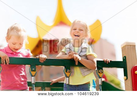 summer, childhood, leisure, friendship and people concept - happy little girls laughing on children playground climbing frame