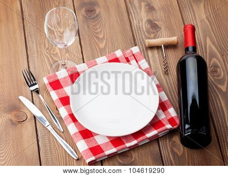 Table setting with empty plate, wine glass and red wine bottle. Top view over rustic wooden table background