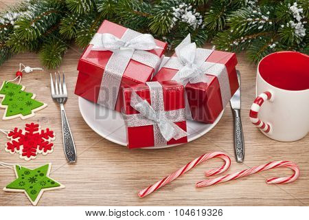 Gift boxes on plate, fir tree and christmas decor over wooden table background