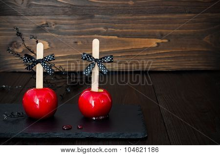 Two red caramel apples. Traditional dessert recipe for Halloween party. Selective focus. Copy space
