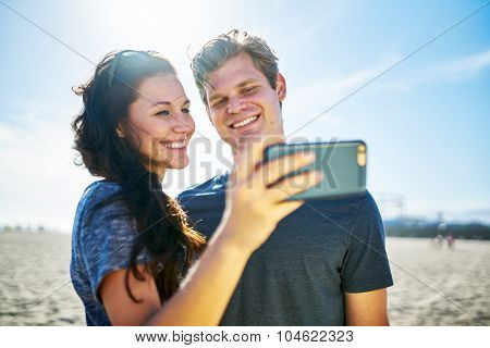 happy couple taking selfie on beach during sunny day with lens flare and shot with selective focus