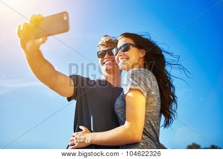 couple selfie with lens flare on clear summer day and wearing sunglasses with lens flare and shot with selective focus effect