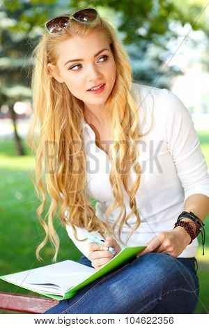 Portrait of beautiful girl with light long hairs in a park.