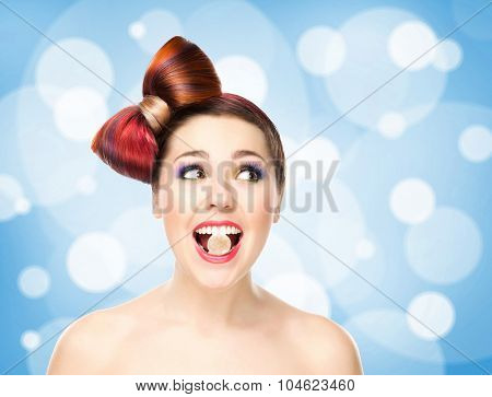 Attractive excited girl with colored hair having candy in mouth on bubbly background.
