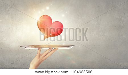Human hand holding tray with red heart on it