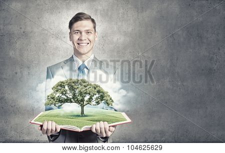Businessman open book with growing tree concept