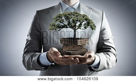 Close up of man holding pile of books with growing green tree in hands