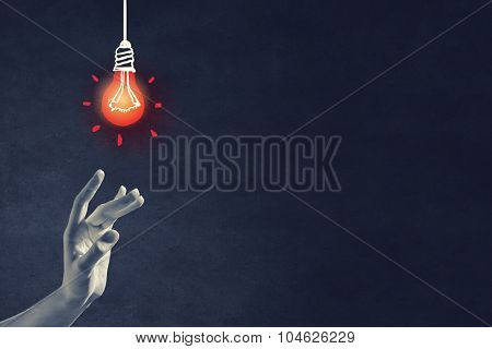 Human hand and light bulb drawn with chalk