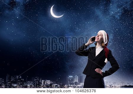 Woman in suit and Santa hat talking on mobile phone