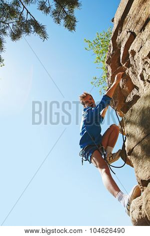 Rappeling lover reaching cliff of mountain