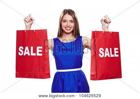 Happy young woman in blue dress showing red paperbags announcing sale