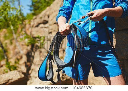 Sportsman preparing climbing equipment before ascending mountain