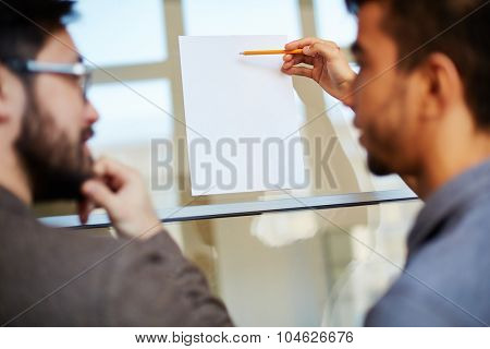 Businessman with pencil pointing at blank paper on board during explanation