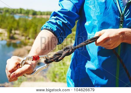 Hands of active man preparing special equipment for climbing