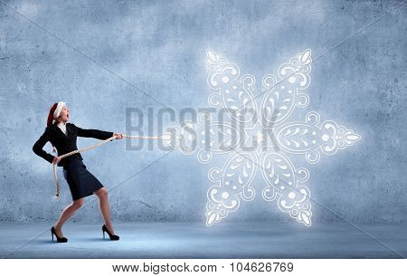 Santa woman pulling white snowflake on rope