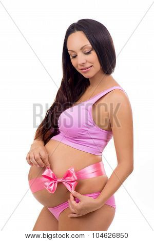 Slim Smiling Pregnant Girl In A Pink Lingerie Ties A Pink Bow On Pregnant Tummy