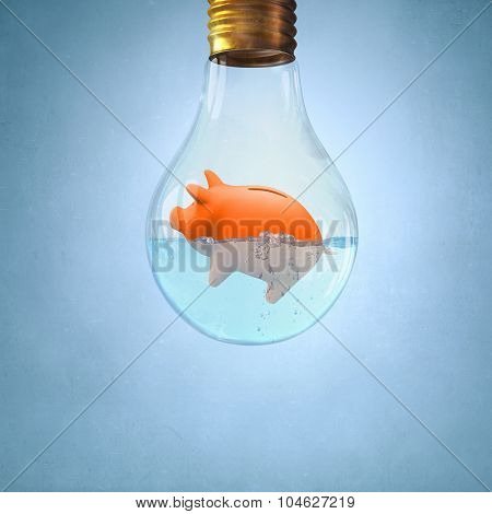Glass light bulb with piggybank floating in water