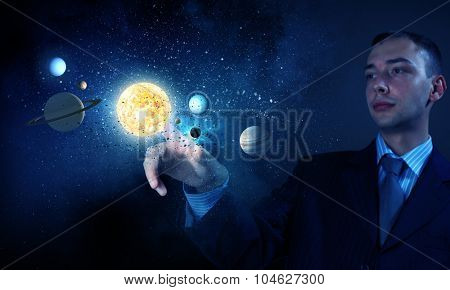 Young businessman touching with finger planet of sun system