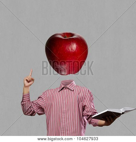 Businessman with book in hand and apple instead of head