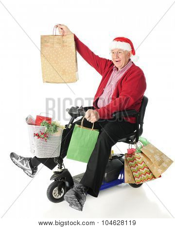 A senior man delightedly riding a scooter loaded with Christmas gifts.  On a white background.