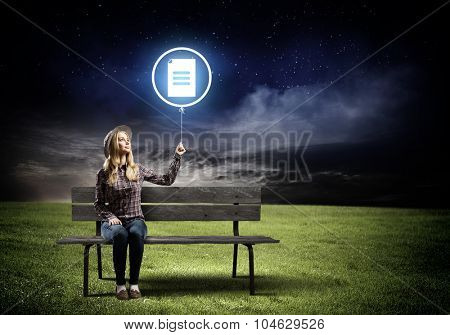 Young woman in casual sitting on bench and holding glowing balloon