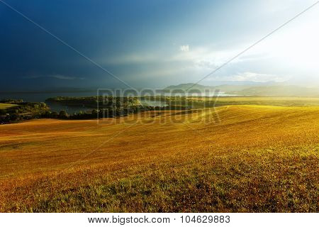 Idyllic summer landscape with clear mountain lake  and green and yellow meadow. Central Europe