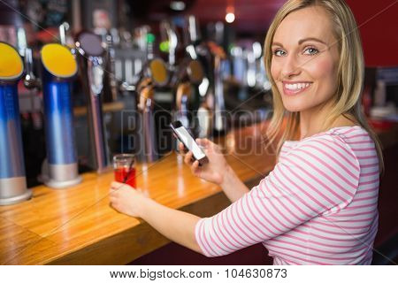 Portrait of young woman with mobile phone holding glass at bar counter