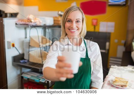 Portrait of happy female shop owner holding glass in bakery