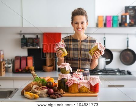 Happy Woman In Kitchen Holding Jars Of Preserved Vegetables