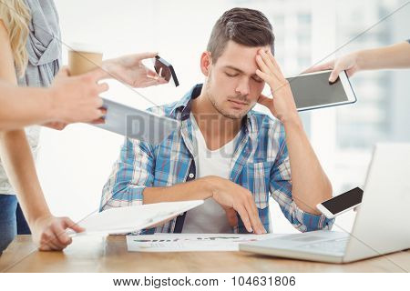 Depressed businessman with head in hand while sitting at desk