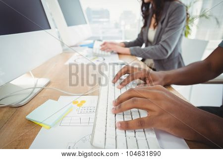 Cropped hands typing on keyboard at computer desk with coworker in office