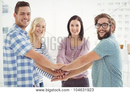Portrait of smiling business people putting their hands together in office