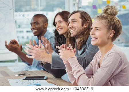 Happy business people clapping at desk in office