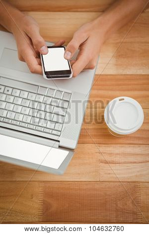 Overhead view of man using mobile phone while laptop and disposable cup on desk in office