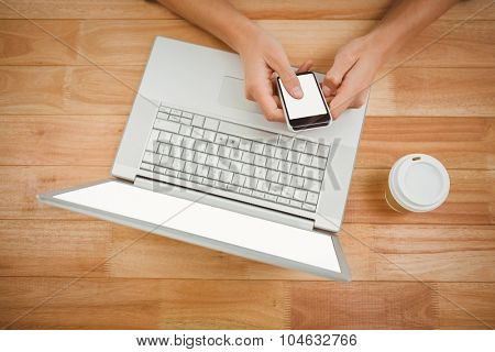 Overhead view of man using smartphone while laptop and disposable cup on desk in office