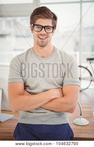 Portrait of hipster wearing eye glasses with arms crossed smiling while leaning at desk in office