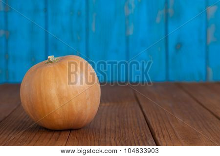Orange pumpkin on blue wooden background, with empty space for text. Autumn scene