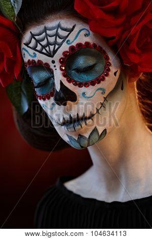 Closeup portrait of woman in santa muerte mask at halloween, eyes closed.