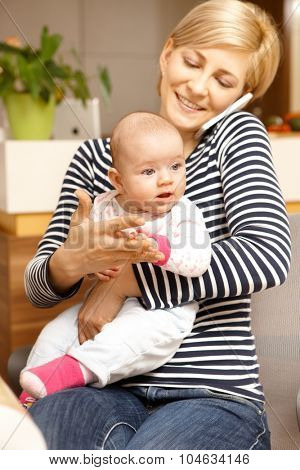 Young mother holding baby girl on lap, talking on mobile phone.