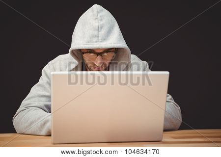 Creative businessman with hooded shirt working on laptop at desk in office