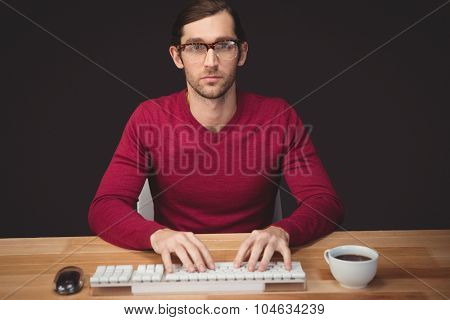 Portrait of serious man typing on keyboard with coffee on desk in office