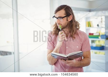 Thoughtful hipster holding pen and book while standing by window in office
