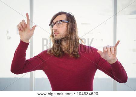 Creative businessman gesturing against window in office