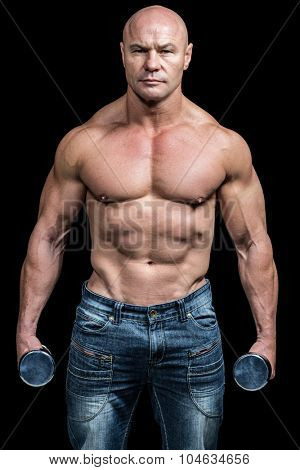 Portrait of bodybuilder holding dumbbells against black background