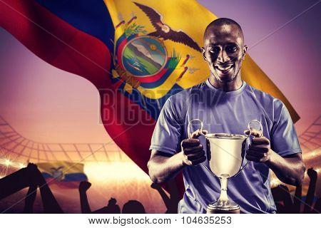 Portrait of happy athlete holding trophy against large football stadium under purple sky
